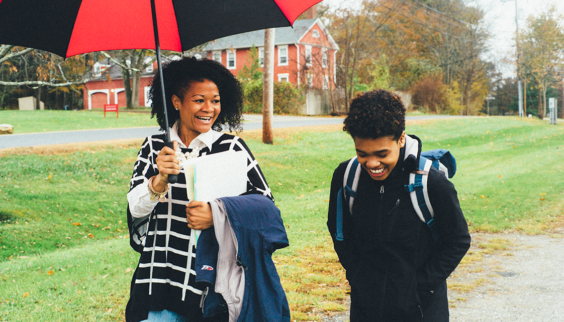 Eden-Reneé Hayes walking with student under umbrella