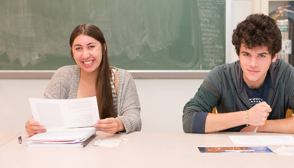 Male and female student smiling in class