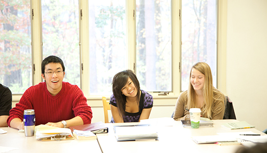 Three latin students smiling in classroom.