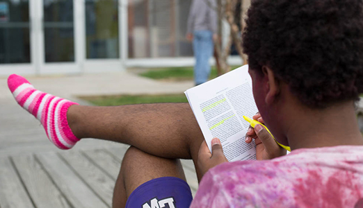 Student in pink socks reads about philosophy on campus.