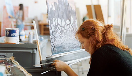 A femaale student works during her painting studio.