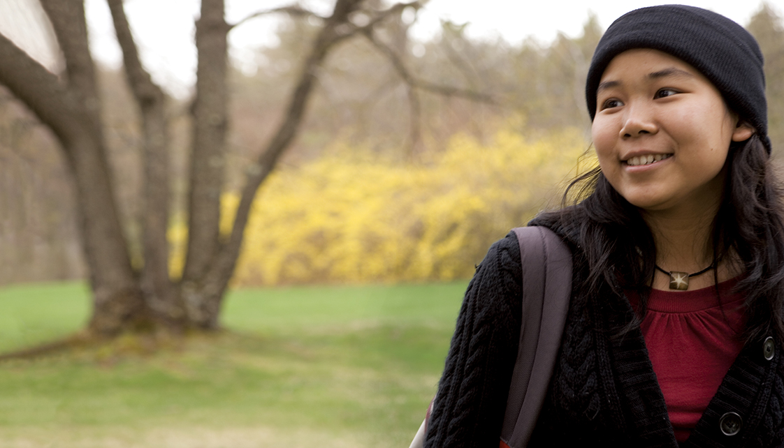 Female student in knit hat smiling on campus.