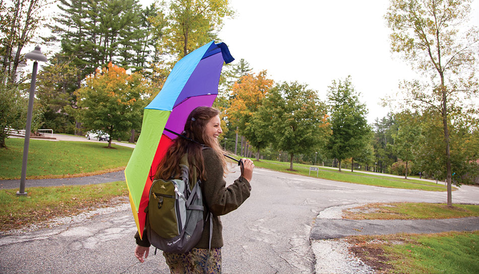 Female student with rainbow umbrella walking to class on a rainy day