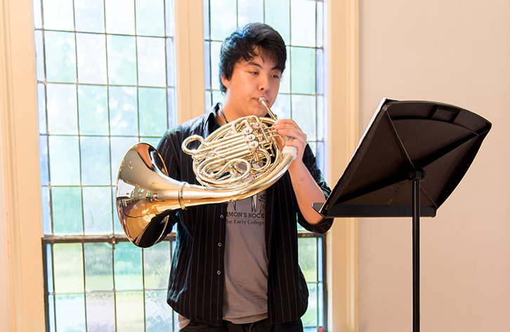 A student practices the French horn.
