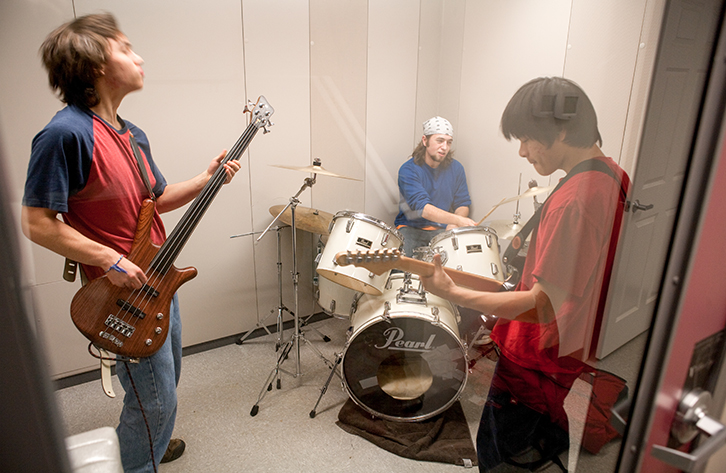 Boys at band practice in a sound-proof booth.