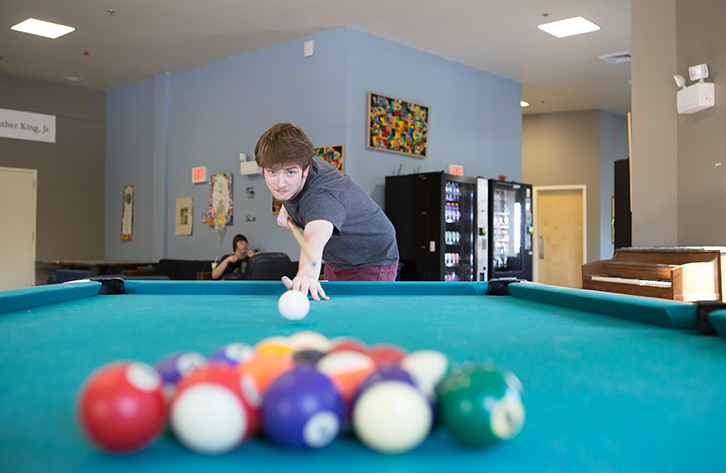 A student plays pool.